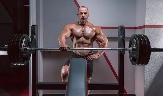 Muscular man stands near the barbell. bodybuilding concept.