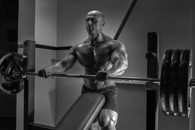 Мускулистый мужчина стоит возле штанги. концепция бодибилдинга. смешанная техника