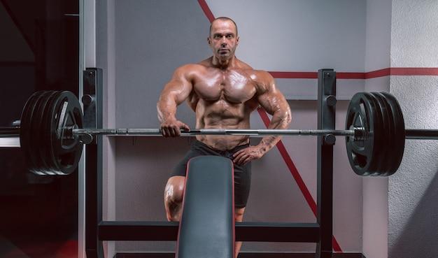 Мускулистый мужчина стоит возле штанги. концепция бодибилдинга.