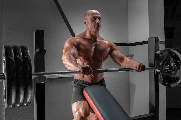 Мускулистый мужчина стоит возле штанги. концепция бодибилдинга. Premium Фотографии