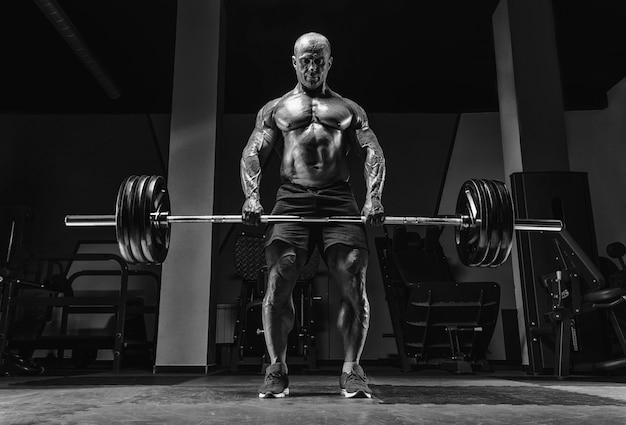 Мускулистый мужчина стоит со штангой в руках. тяга. концепция бодибилдинга. смешанная техника