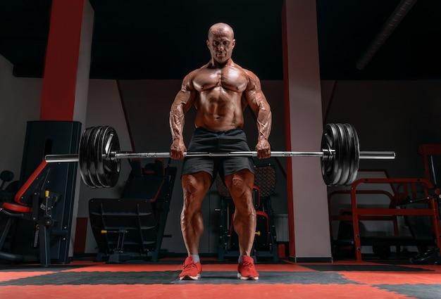 Мускулистый мужчина стоит со штангой в руках. тяга. концепция бодибилдинга. Premium Фотографии