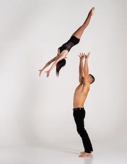 Мускулистый мужчина подбрасывает женщин в воздух
