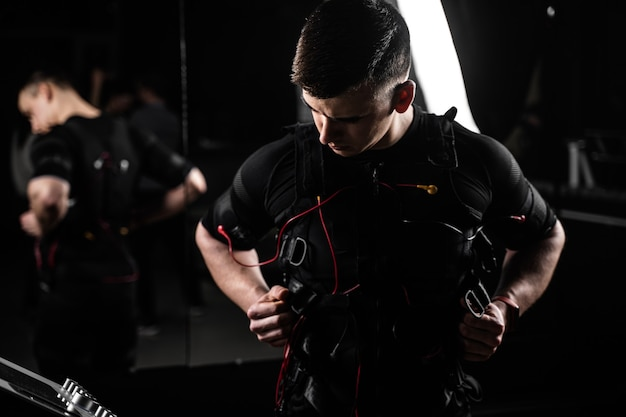 Muscular man trainer weared ems electrical body suit in gym