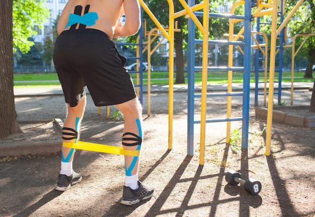 スポーツグラウンドで脚にフィットネス抵抗バンドをトレーニングする筋肉の男。屋外でのボディトレーニングに弾性運動学テーピングを施した、認識できない若いボディービルダーの背面図。