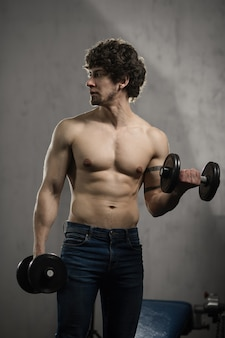 Muscular man trains biceps dumbbells in the gym, hand training