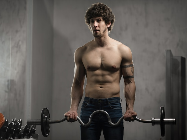 Muscular man trains biceps with barbell in the gym, hand training