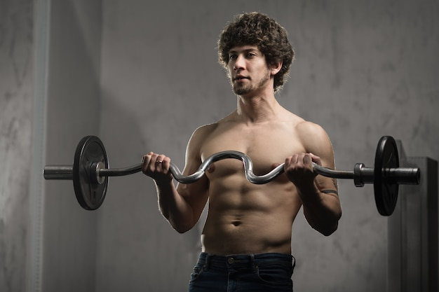 Muscular man trains biceps with barbell in the gym