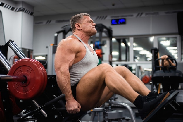 Muscular man trains his legs in the gym.