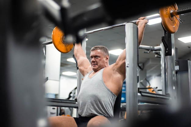Muscular man trains his shoulders with a barbell in the gym.
