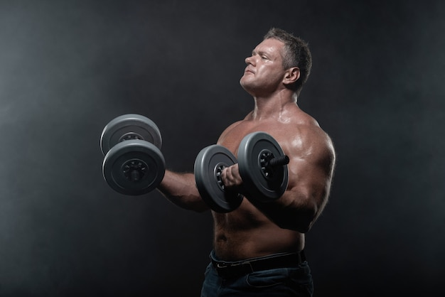 Muscular man trains with dumbbells on black background in smoke