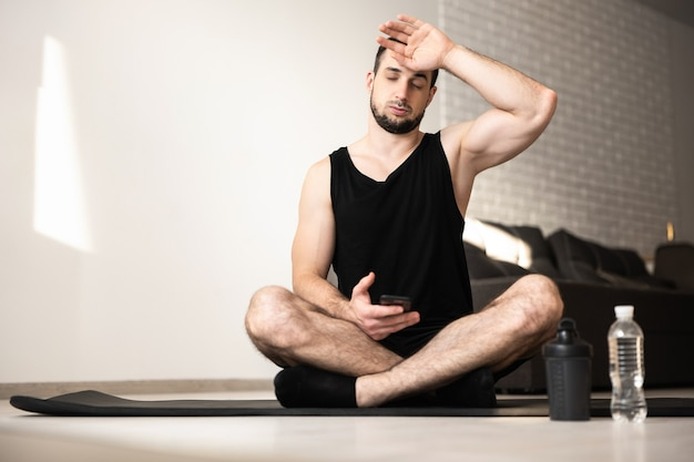 Muscular man wipes sweat of his forehead after hard home workout. healthy lifestyle concept. man tired after intensive training. plastic water bottle. light living room on background.