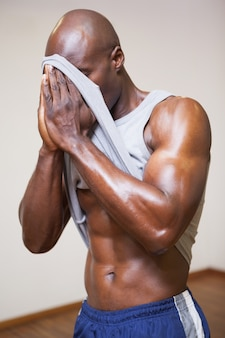 Muscular man wiping sweat after workout in gym