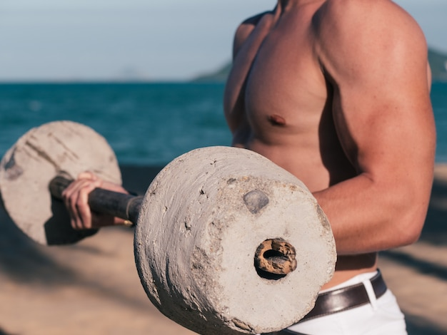 Muscular man with barbell closeup on the beach