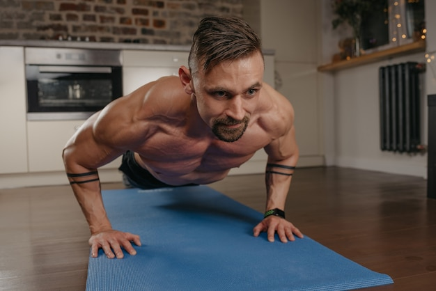 A muscular man with a beard is doing pushups on a blue yoga mat in his apartment in the evening