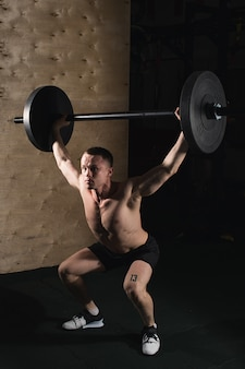 Muscular man with beard train with barbell raised over head in gym
