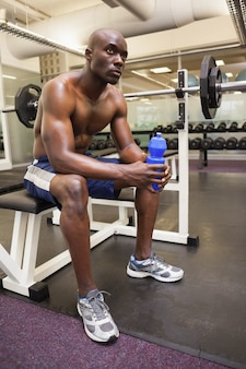 Muscular man with energy drink in gym