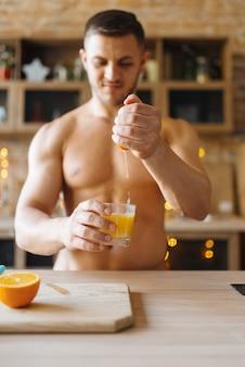 キッチンでオレンジジュースを調理する裸の体と筋肉の男。自宅で朝食を準備している裸の男性人、衣服なしの食事の準備