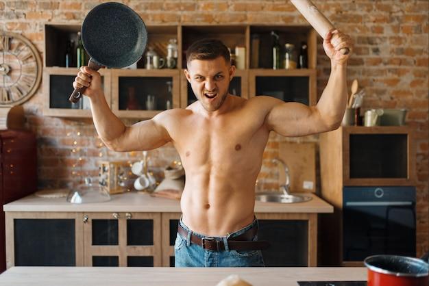 벗은 몸을 가진 근육질의 남자는 부엌에 프라이팬과 롤링 핀을 보유하고 있습니다. 집에서 아침 식사를 준비하는 누드 남성 사람, 옷없이 음식 준비