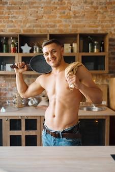 벌거 벗은 몸매를 가진 근육질의 남자는 부엌에 프라이팬을 보유하고 있습니다. 집에서 아침 식사를 준비하는 누드 남성 사람, 옷없이 음식 준비