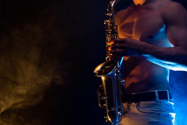 Мускулистый мужчина с обнаженным торсом играет на саксофоне с дымом