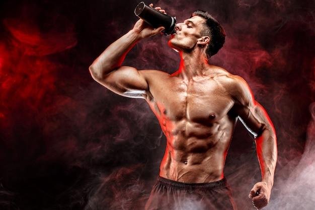 통에 단백질 음료와 함께 근육 질의 남자