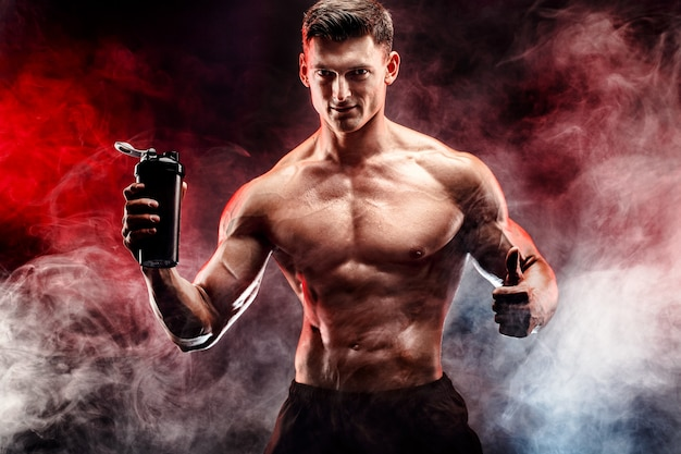Muscular man with protein drink in shaker