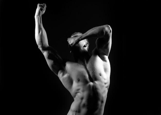 セクシーな体を持つ筋肉質の男。黒、白。上半身裸の男。裸の胴体を持つ筋肉のセクシーな男。手と裸の胸に静脈を持って力でポーズをとっているアスリートボディービルダーのセクシーな筋肉質の男性の胴体。