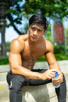 Muscular man without clothes sitting poses holding a drinking bottle while exercising outdoors in the park