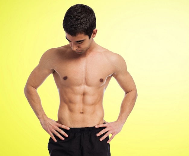 Muscular man without shirt with yellow background