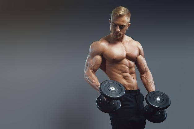 어두운 회색 배경에 아령으로 운동을 하는 근육질의 남자. 강한 남성 알몸 몸통 복근