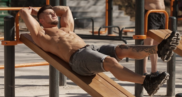 胃の運動を行うワークアウト筋肉男は屋外です。強い男性の裸の胴体abs