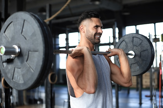 Muscular man working out in gym doing exercises with barbell at biceps.