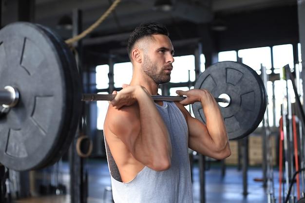 팔뚝에서 바벨 운동을 하는 체육관에서 운동하는 근육질의 남자.