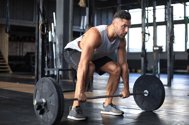 上腕二頭筋でバーベルを使ってエクササイズをしているジムで運動している筋肉の男。