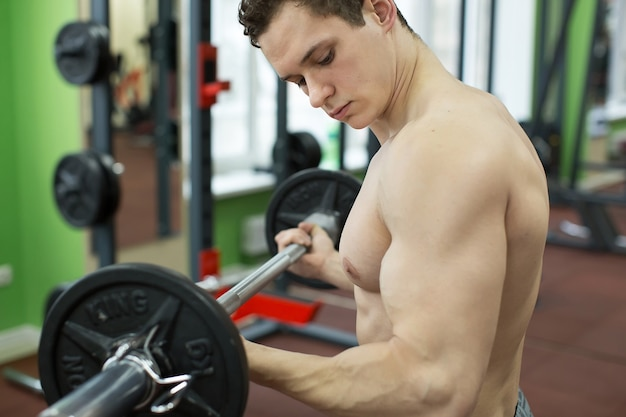 バーベル、強い男性の裸の胴体腹筋でエクササイズをしているジムで働いている筋肉の男