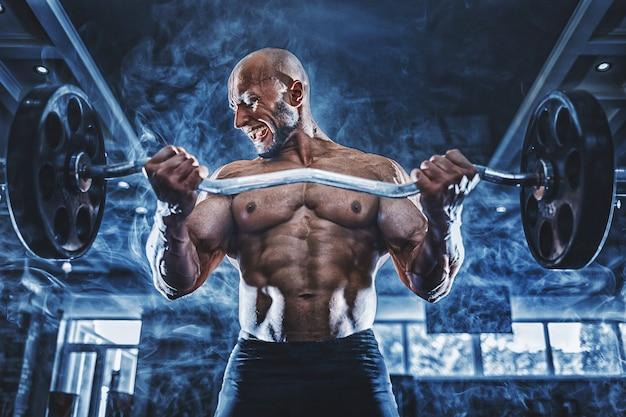 ダンベルでエクササイズをしているジムで運動している筋肉の男