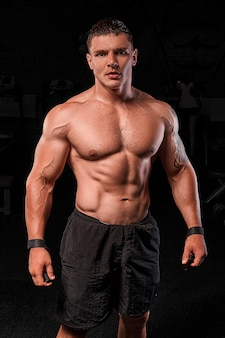 Мускулистый мужчина, тренирующийся в тренажерном зале, сильный мужчина, черный фон