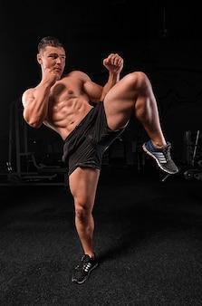 ジムで運動している筋肉の男、強い男性、背景は黒です