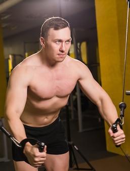 ジムで運動する筋肉の男