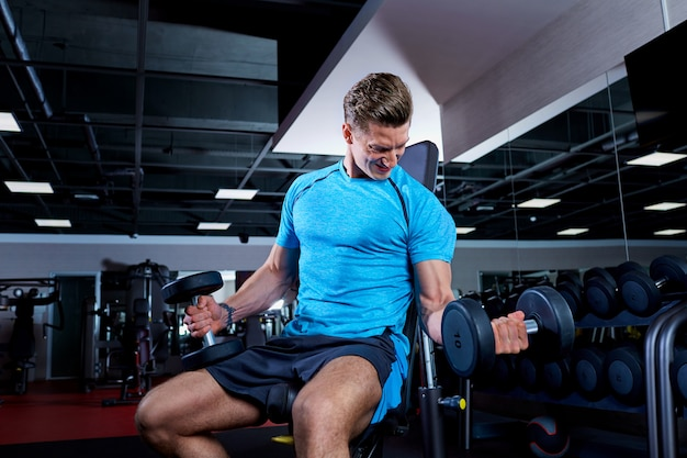 Muscular man working out with dumbbells in gym