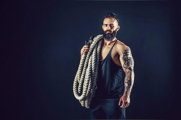 太いロープで運動する筋肉質の男性裸の胴体の強さとモチベーションを持つ男性の写真