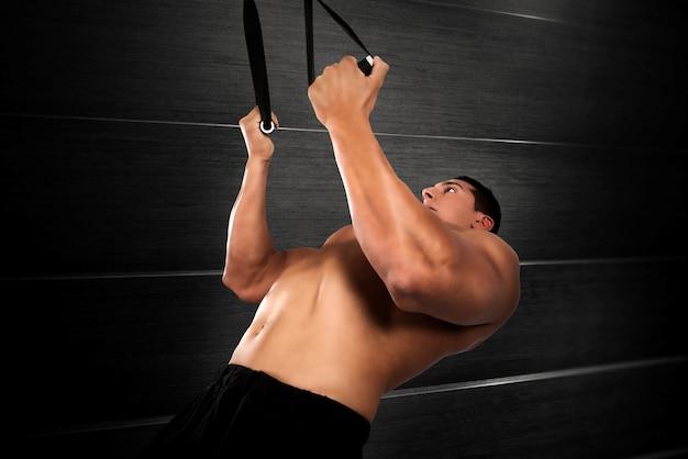 Trx의 밴드와 함께 근육 질의 남자 운동
