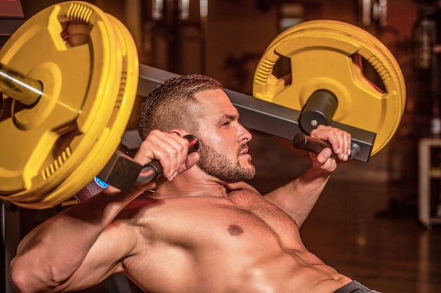 Muscular man workout with barbell at gym. bodybuilder athletic man with six pack, perfect abs, shoulders, biceps, triceps, chest. barbells workout. athletic guy standing with barbell, workout in gym.