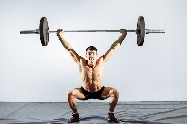 Muscular man workout with barbell at gym.