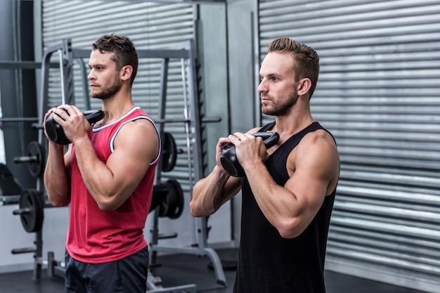 Muscular men exercising with kettlebells