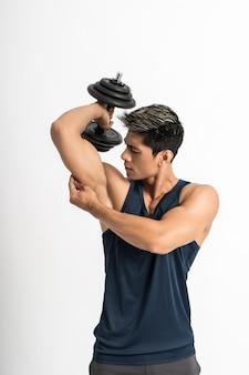 筋肉質の男性が上腕三頭筋をトレーニングするためにダンベルウェイトを持ち上げる