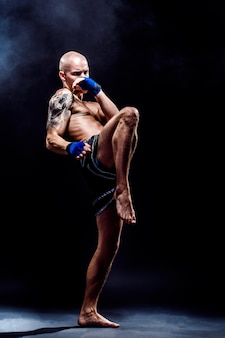 Muscular muay thai fighter punching in darkness