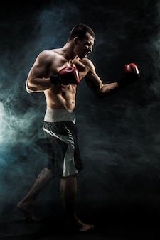 Muscular muay thai fighter punching in smoke