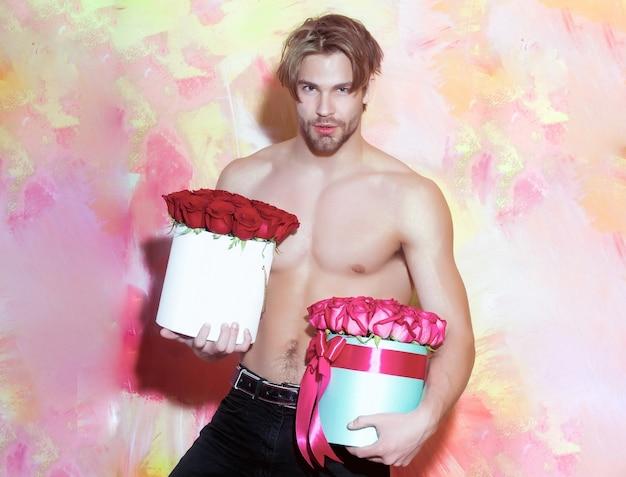 섹시한 몸매를 가진 근육질의 벌거 벗은 남자가 빨간 장미 상자를 보유하고 있습니다.